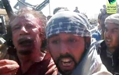 """Bị thương và dường như sửng sốt, Gaddafi có vẻ không biết điều gì đang chờ mình khi hỏi người bắt giữ: """"Tôi phải làm gì cho anh?"""". Vài giây sau Gaddafi cầu xin tha mạng nhưng đã bị bắn chết. Một đoạn phim khác ghi lại cảnh thi thể đầy máu của ông này bị kéo lê qua các đường phố ở thành phố quê hương Sirte, rồi sau đó được đem đi diễu hành trước đám đông gần thành phố cảng Misrata."""