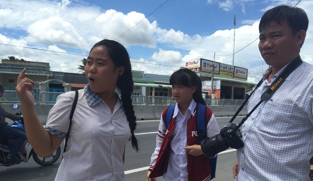 Học sinh băng qua đầu xe tải trên quốc lộ