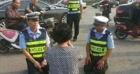 Cảnh sát quỳ xuống đất, giảng luật cho người vi phạm