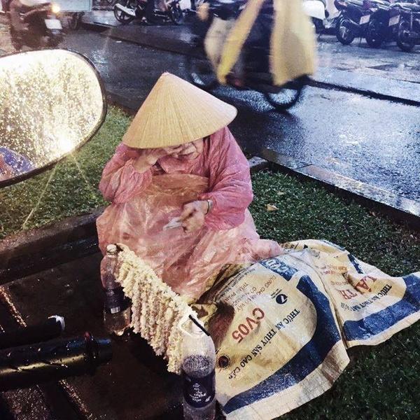 Bà cụ ngồi giữa mưa lớn bán hoa mưu sinh ở Sài Gòn