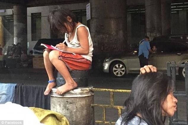 Bé gái ngồi giữa đường học bài làm động lòng trắc ẩn