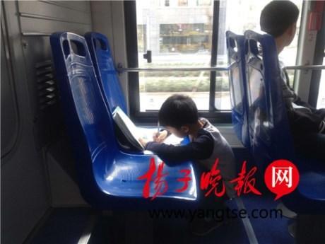 Ảnh cậu bé 9 tuổi làm bài trên xe buýt khiến người lớn suy ngẫm - ảnh 1