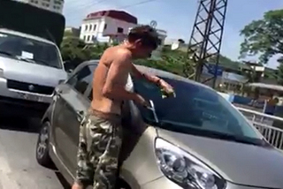 Người nước ngoài lau kính cho xe ô tô dừng đèn đỏ giữa trời nắng gắt tại Thủ đô