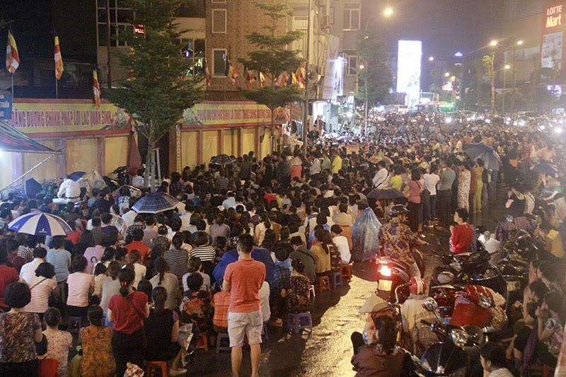 Saat hujan, ribuan warga Vietnam melakukan puja bakti Hari Ullambana di jalan di depan Vihara Phuc Khanh, Hanoi, Vietnam.