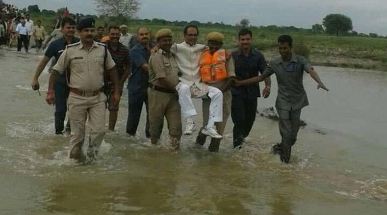 Quan chức được cảnh sát khiêng qua dòng nước lũ