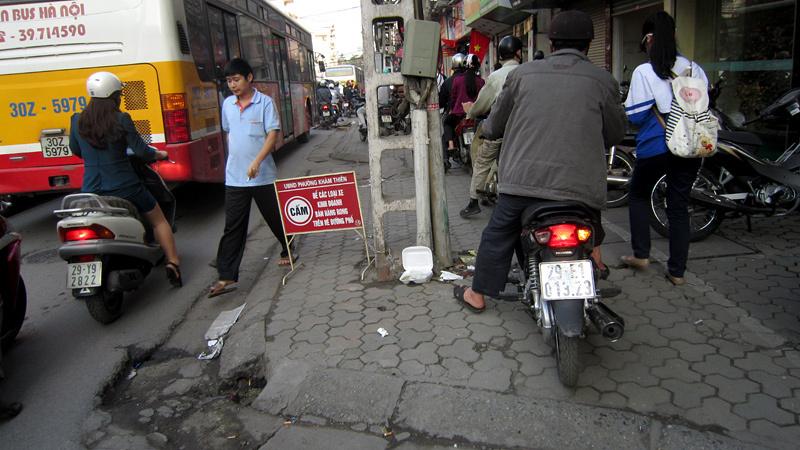 Người đi bộ bước xuống lòng đường phố Lê Duẩn để... nhường vỉa hè cho dòng xe máy đang hối hả di chuyển.