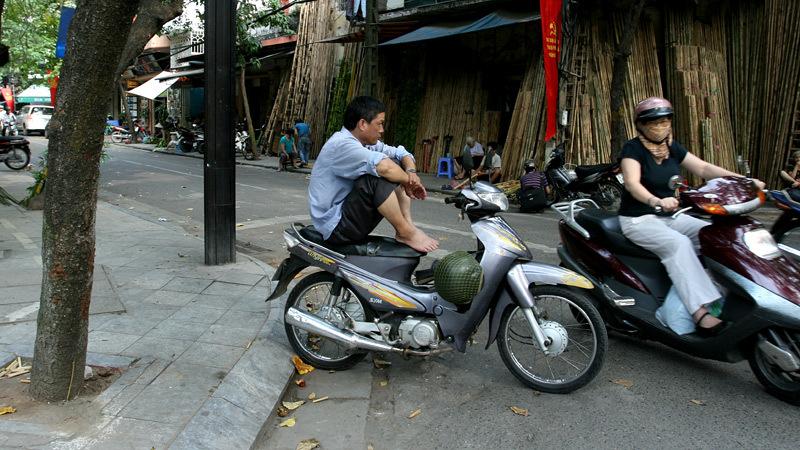 Điểm chờ khách của những người hành nghề xe ôm trên phố Hàng Vải nằm giữa lòng đường vì vỉa hè được ngầm mặc định thuộc sở hữu của các hộ kinh doanh.