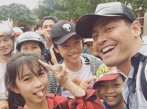 MC Phan Anh chụp hình với các em nhỏ ở Mai Hóa - Thạch Hóa (Ảnh: FBNV)