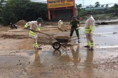 Cảnh sát đội mưa dọn đất đá ngổn ngang sau lũ