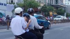 Học sinh vừa đi đường vừa xúc cơm ăn ngay trên xe máy