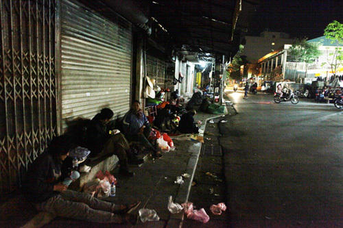 Người vô gia cư mặc áo mưa chống rét, ngủ trên vỉa hè