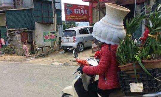 Người phụ nữ đi xe máy đội cả chậu hoa trên đầu