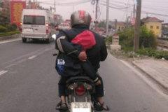 Người cha vừa lái xe máy vừa ôm con ngủ trên đường quốc lộ