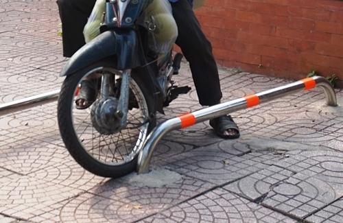 Người Sài Gòn lạng lách xe máy trên vỉa hè có barie chắn ngang