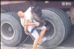 Người mẹ địu con nhỏ tháo lốp xe tải