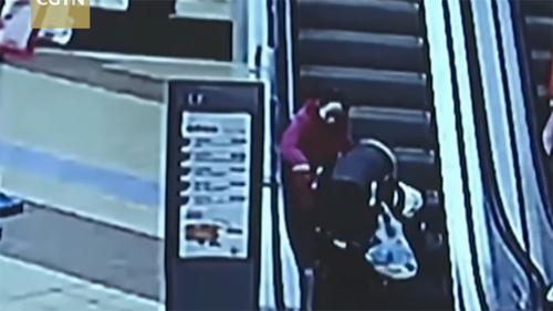 Mẹ cố đẩy xe nôi lên thang cuốn, xe lật ngược rơi con ra ngoài