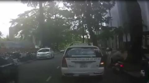 Mở cửa taxi hất người đi xe máy ngã nhào