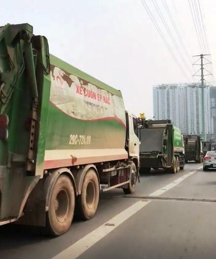 Xe chở rác nối đuôi nhau chạy vào làn buýt nhanh