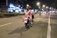 Hai đứa trẻ ngồi ngược trên yên xe máy phóng vun vút ở Hà Nội