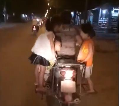 Người phụ nữ để 3 đứa trẻ đứng sau xe máy lao vun vút trên đường