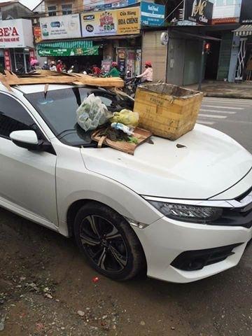 Ô tô đậu trước lối vào nhà dân bị đổ rác đầy nắp ca pô