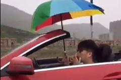 Thanh niên sành điệu lái xe mui trần cầm ô che mưa