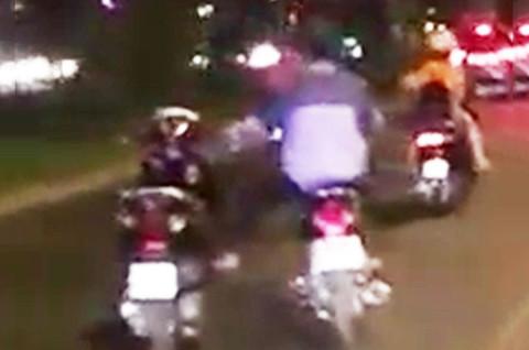 Thanh niên một mình lái hai xe máy trên đường