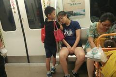 Cảm động bé trai dùng tay làm gối cho mẹ ngủ trên tàu điện