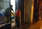 Mưa sầm sập, người Hà Nội xắn quần tát nước ra khỏi nhà