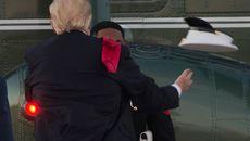 Ông Trump khom người nhặt mũ cho lính gác