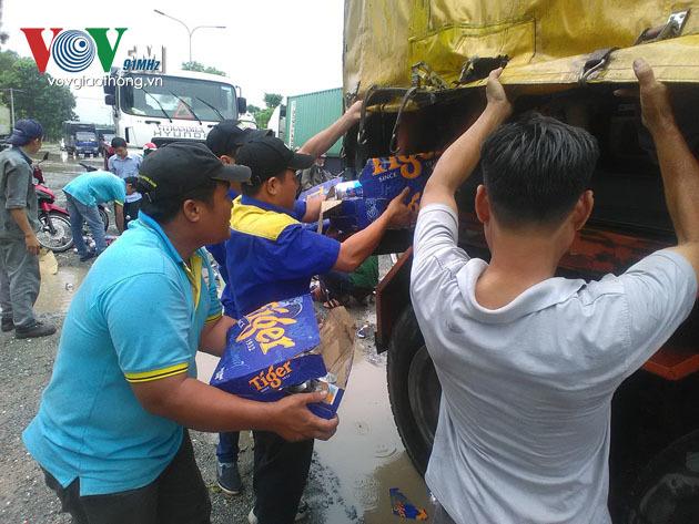 Hàng chục người dân giúp tài xế thu dọn bia đổ xuống đường