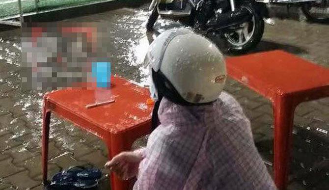 Cô vợ mặc áo mưa đợi chồng đá bóng gây tranh cãi trên mạng xã hội