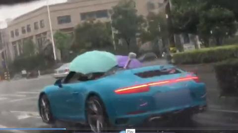 Bi hài cảnh 'dân chơi' lái siêu xe Porsche mui trần cầm ô che mưa