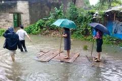 Nữ chủ tịch phường cầm ô đứng trên bè, được kéo đi thị sát lụt