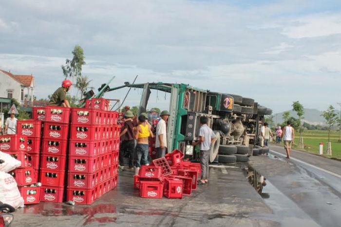 Lật xe chở bia, người dân giúp tài xế nhặt lại hàng