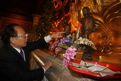 Bộ trưởng Văn hóa nhặt tiền lễ cho vào hòm công đức